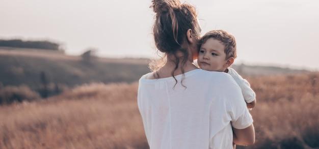 若い女性は日没で牧草地で晴れた日に彼女の幼い息子にキスします。若い母親が彼女の赤ん坊を保持しています。母と幼い息子が自然の中で楽しい時間を過ごしています。
