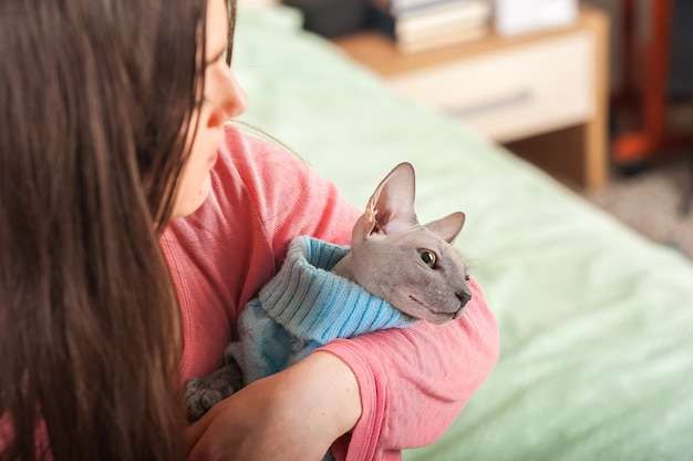 Young woman kisses and hugs the sphinx at home close-up and copy space. pets and people.