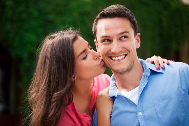 Молодая женщина целует своего парня в щеку