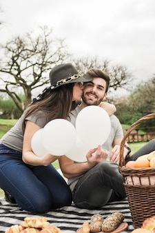 Young woman kissing her boyfriend at picnic in the park