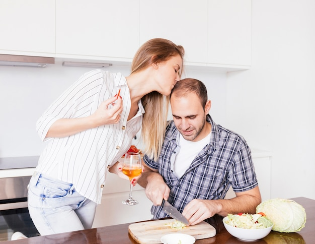 Young woman kissing her husband's forehead cutting the cabbage with knife
