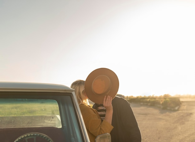 Young woman kissing her partnerbehind the hat