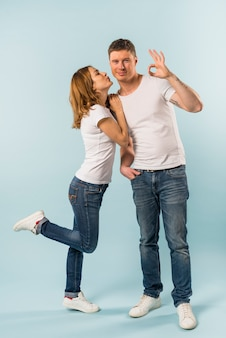 Young woman kissing her smiling boyfriend showing ok sign against blue backdrop
