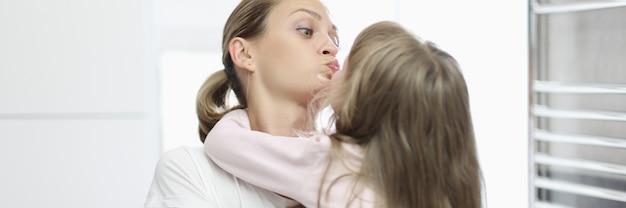 욕실에서 어린 소녀를 키스 하는 젊은 여자