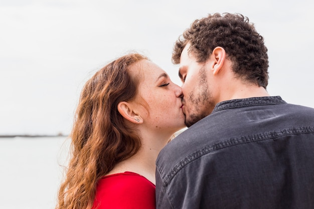 Young woman kissing man on sea shore