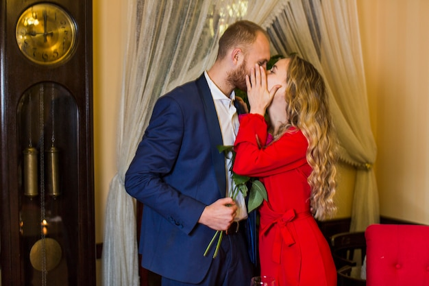 Young woman kissing man with flowers on lips