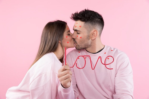 Young woman kissing man with paper hearts on faces and love sign