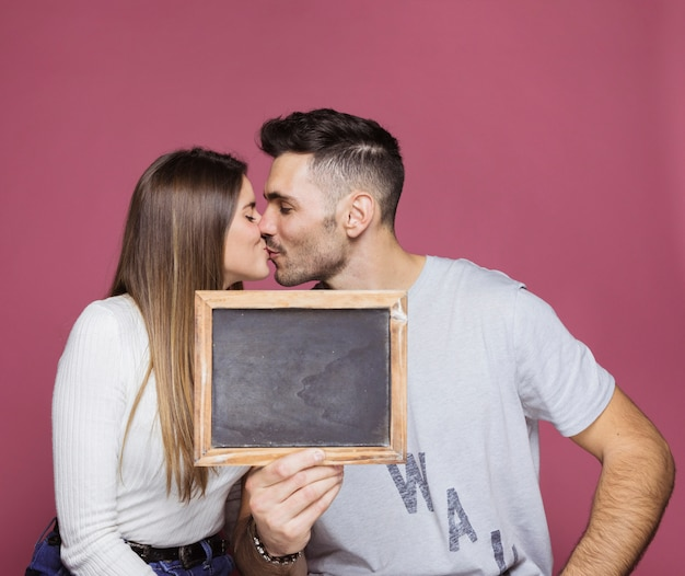Young woman kissing with positive man and showing photo frame