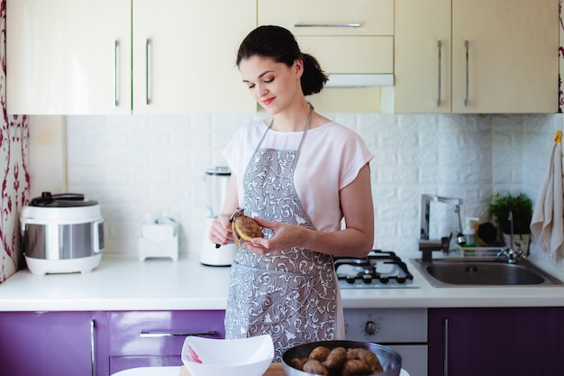 Young woman in kitchen in apron peeling potatoes