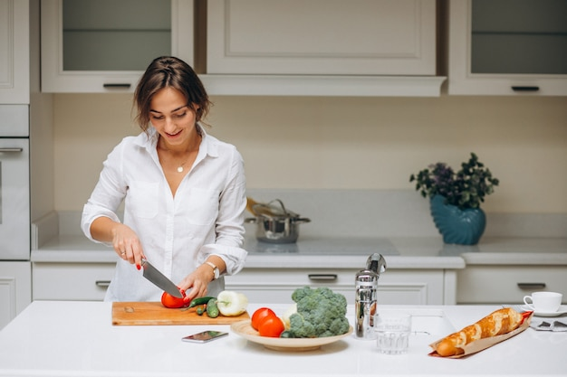Young woman at kitchen cooking breakfast