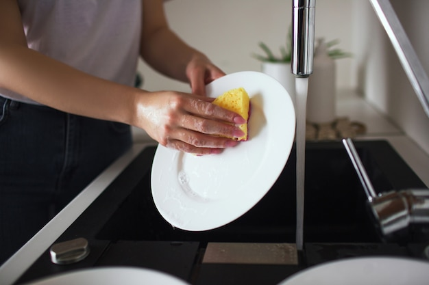 Young woman in kitchen during quarantine. whshing white plates with sponge and dishwasher. cleaning dishes alone in kitchen. cut view.