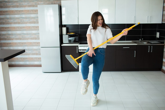 Young woman on kitchen. holding broom in hands as musical instrument and pretend to play on it. have fun alone after cleaning floor.