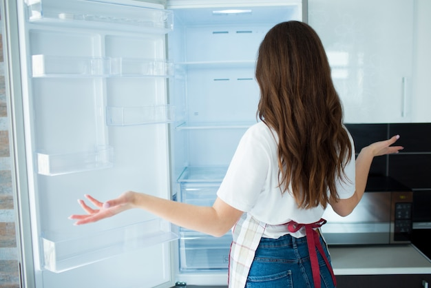 Young woman on kitchen. look at empty fridge shelves with no food on it. hungry and can't cook. back view of woman doesn't know what to do.