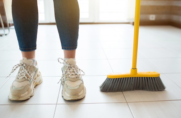 Young woman in kitchen. stand alone after sweeping floor. hold broom with hand. householding on free time.