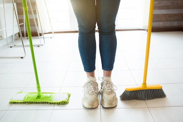 Young woman on kitchen. stand on floor with green mop and yellow broom. cleaning time during daylight. alone in kitchen. cut view.