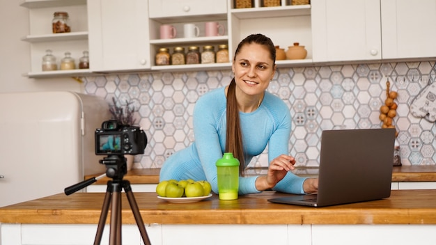 Young woman in kitchen with laptop smiling. food blogger concept. a woman is recording a video about healthy eating. camera on a tripod.
