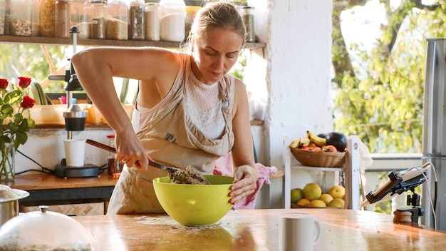 Young woman kneading dough for homemade whole grain rye bread in green plastic bowl