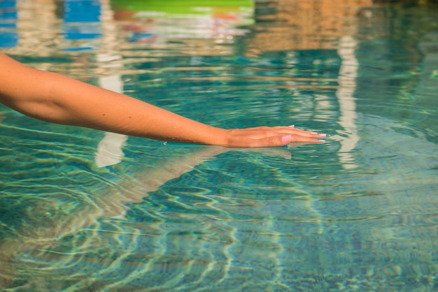 Young woman kneeling by the edge of a swimming pool, touching the calm water with her hand.