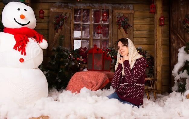 Молодая женщина на коленях на полу в модной зимней одежде с шарфом на голове, с хлопком возле большого снеговика и других рождественских украшений.