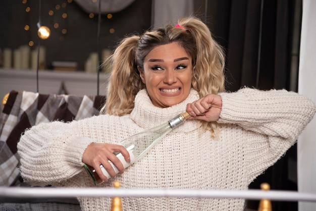 Giovane donna in maglione lavorato a maglia apertura champagne.