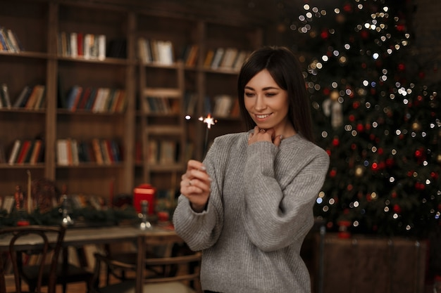 Young woman in a knitted warm sweater holds a sparkler in her hand  smiles and looks at it near of a vintage bookcase in a festive room. joyful girl.