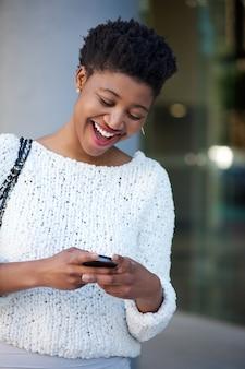 웃으면 서 핸드폰에 문자 메시지를 읽는 젊은 여자
