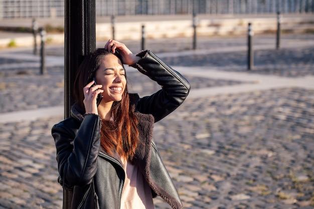 Молодая женщина смеется и разговаривает по телефону