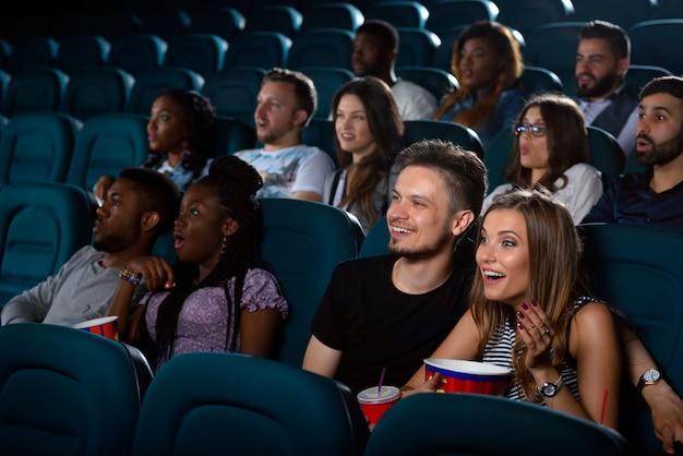 Молодая женщина взволнованно смеется во время просмотра фильма со своим парнем в местном кинотеатре