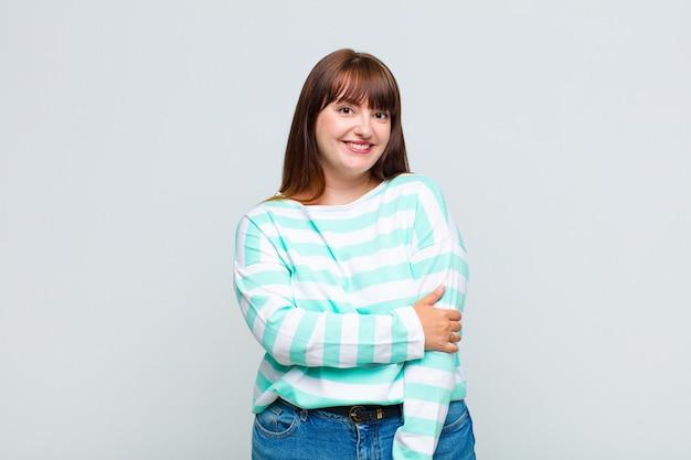 친절하고 긍정적이지만 불안한 태도로 수줍어하고 유쾌하게 웃고있는 젊은 여성
