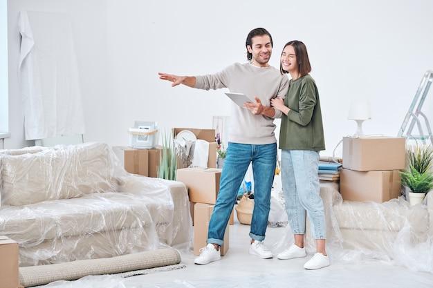 Молодая женщина смеется, стоя рядом с мужем с тачпадом, объясняя ей, какую мебель он хотел бы поставить в гостиной