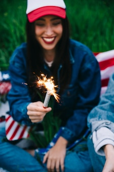 Young woman laughing with firework in hand