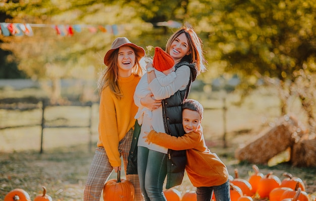 Young woman laughing with her three cute kids at the pumpkin's field. autumn background.
