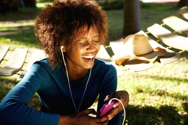 Young woman laughing with mobile phone and earphones