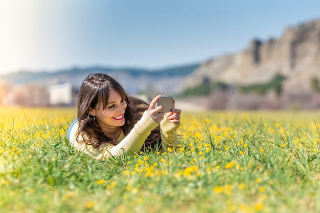 Young woman laying down using mobile phone.