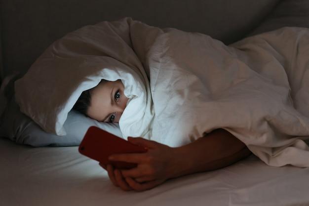 携帯電話を見つめながら、夜ベッドに横たわる若い女性。 Premium写真