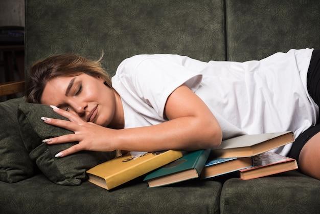 本でいっぱいのソファに横たわっている若い女性。