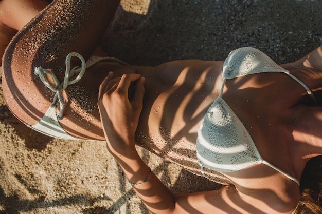 ヤシの木の葉の下の砂浜に横たわる若い女性