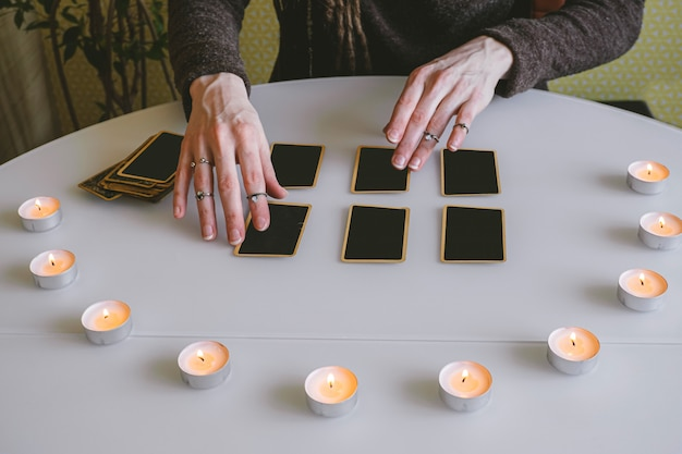 Young woman lays out black cards on the table with candle lights