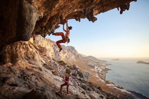 아름 다운 전망 동굴에서 등반하는 젊은 여자 리드