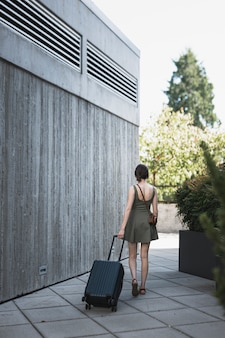Молодая женщина ведет чемодан