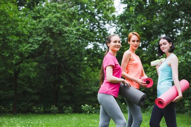 自然公園でヨガをリードする若い女性