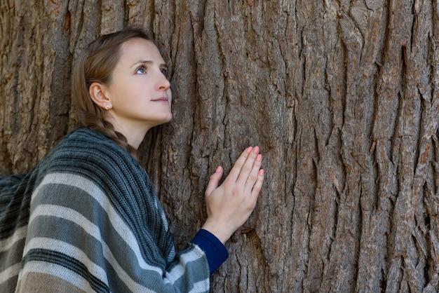 Молодая женщина прислонилась к стволу большого дерева