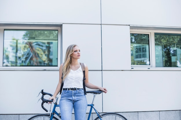 Young woman leaning on bicycle standing near the wall