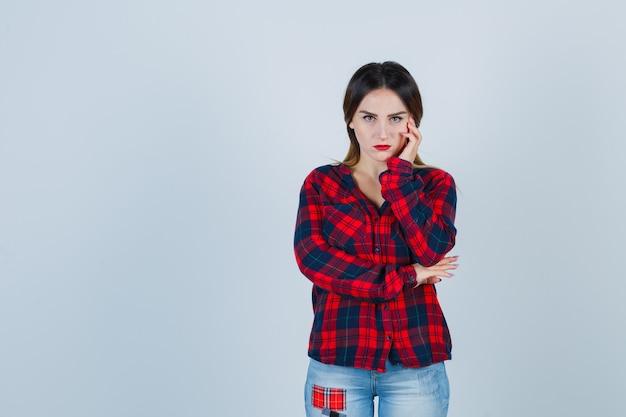 Guancia pendente della giovane donna a disposizione in camicia a quadri, jeans e guardando sconvolto. vista frontale.