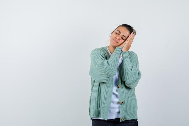 Молодая женщина, опираясь щекой на руки в белой рубашке и мятно-зеленом кардигане, выглядит сонной