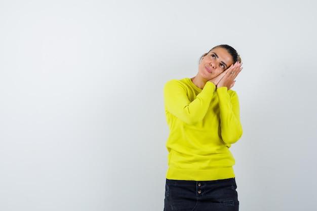 Молодая женщина, опираясь щекой на руки в желтом свитере и черных штанах, выглядит счастливой