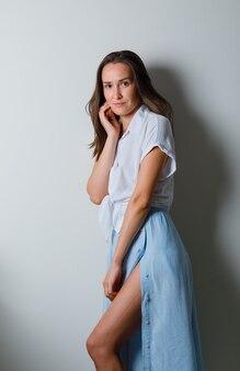 Молодая женщина, опираясь щекой на ладонь и позирует спереди в белой футболке и голубой юбке и выглядя очаровательно