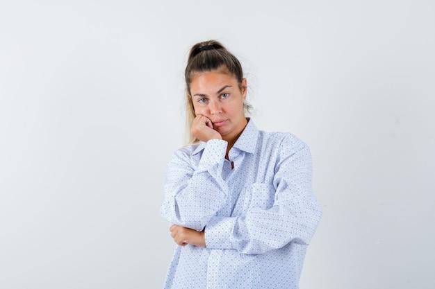 白いシャツでポーズをとって、かわいく見える間、手のひらに頬をもたれている若い女性