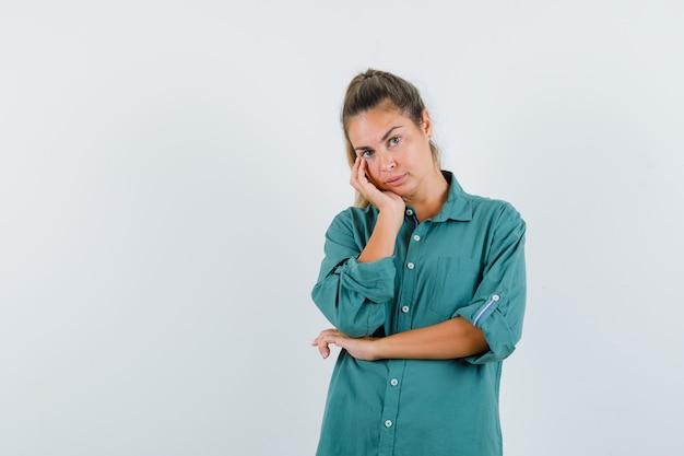 Молодая женщина, опираясь щекой на ладонь, думает о чем-то в зеленой блузке и выглядит задумчиво