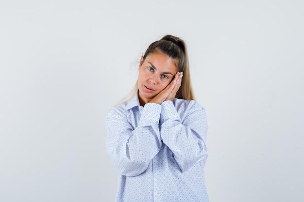 白いシャツの枕のように手のひらに頬をもたれ、かわいく見える若い女性